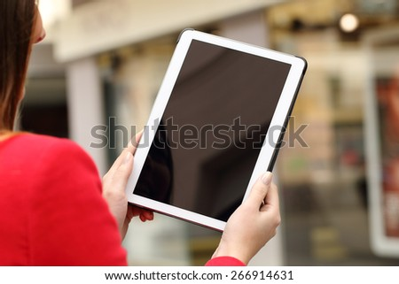 Woman using and showing a blank tablet screen in the street in front a store - stock photo