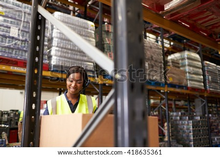Woman using barcode reader in warehouse, head and shoulders