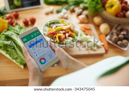 Woman using calorie counter application on her smartphone - stock photo