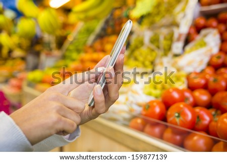 Woman using cell phone while shopping in supermarket, vegetable department store - stock photo