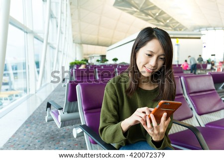 Woman using cellphone and waiting to depart