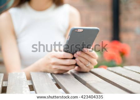 Woman using cellphone at cafe