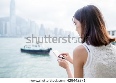 Woman using cellphone at Hong Kong city - stock photo