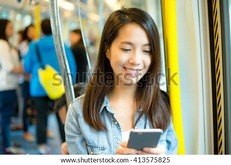 Woman using cellphone in train compartment - stock photo