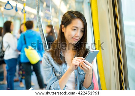 woman using cellphone inside train compartment - stock photo
