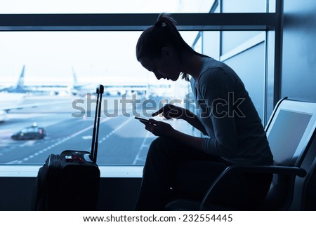 Woman using cellphone mobile in the airport - stock photo