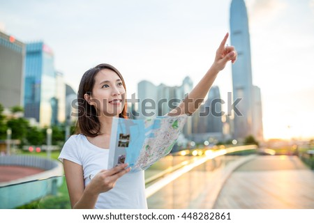 Woman using city map and finger pointing far away - stock photo