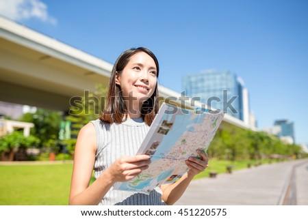Woman using city map in Hong Kong - stock photo