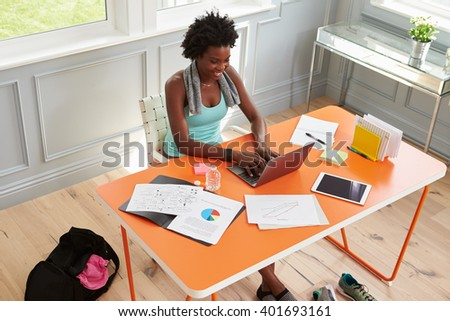 Woman using computer at home after exercising, elevated view - stock photo