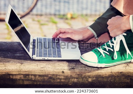 woman using computer in the park - stock photo