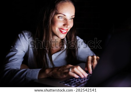 woman using computer late at night - stock photo