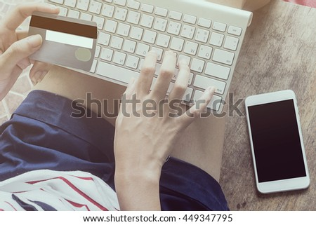 woman using computer to online shopping and pay by credit card, Low light, selective focus on hand, can be used for e-commerce, business, technology and internet concept, vintage color tone - stock photo