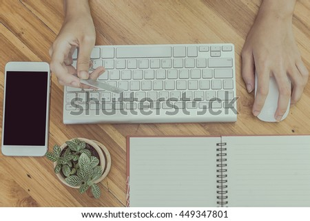 woman using computer to online shopping and pay by credit card, Low light, selective focus on hand, can be used for e-commerce, business, technology and internet concept, Vintage tone filter - stock photo