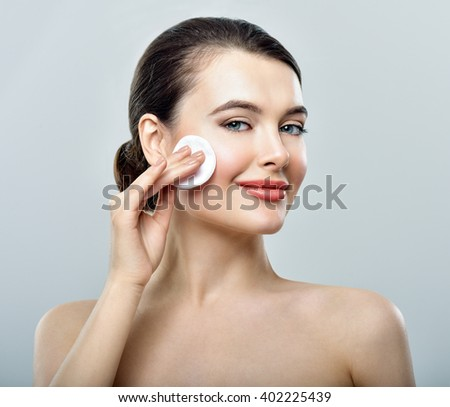 Woman using cotton pad. Happy smiling beautiful young woman cleaning skin by cotton pad. - stock photo