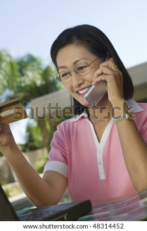 Woman Using Credit Card and Cell Phone for Online Purchase - stock photo