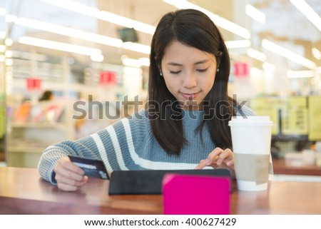 Woman using credit card for paying on tablet pc - stock photo
