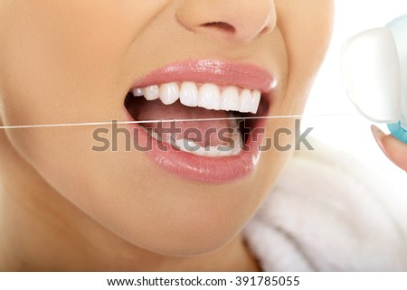 Woman using dental floss.