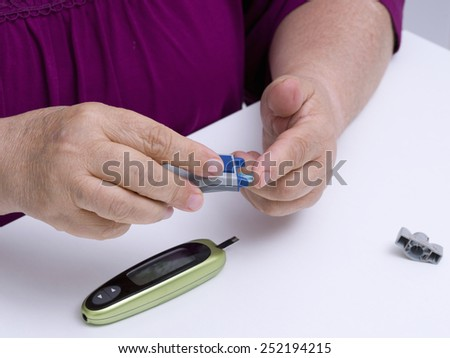 woman using diabetes lancet theck sugar level - stock photo