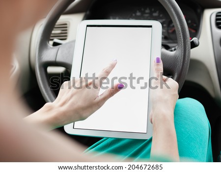Woman using digital tablet in her car - travel and transportation concept. - stock photo