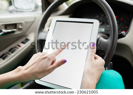 Woman using digital tablet in the car - stock photo