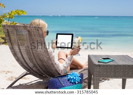 Woman using digital tablet on the beach - stock photo