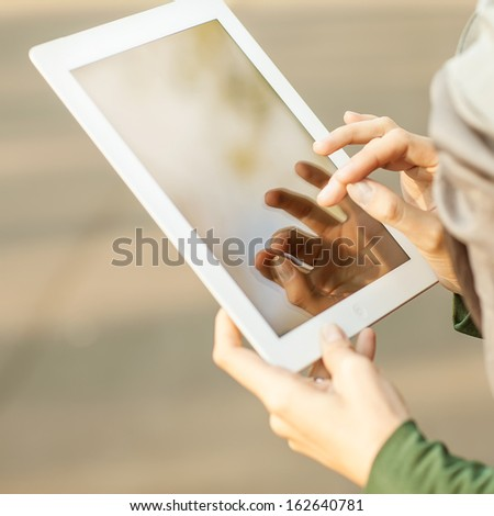 Woman using digital tablet PC in the park. - stock photo