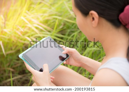Woman using digital tablet PC in the park - stock photo