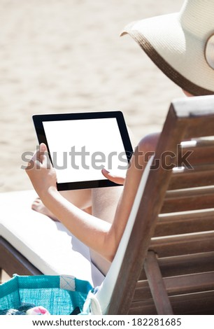 Woman using digital tablet with blank screen while relaxing on beach chair - stock photo