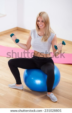 Woman using dumbbells and fitness ball during training