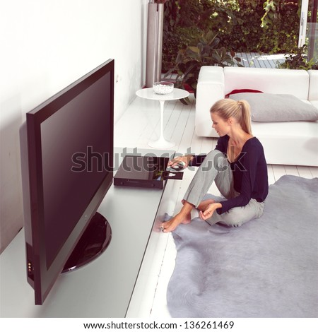 woman using dvd player in living room - stock photo