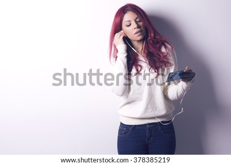 Woman using earphones from smart phone, listening to music or talking to someone