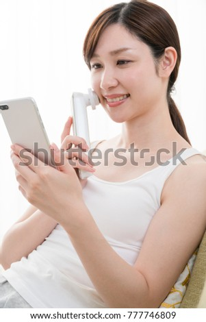 Woman using facial instrument, smartphone