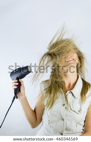 Woman using hairdryer to blow her hair around. She looks happy, cheerful and active.