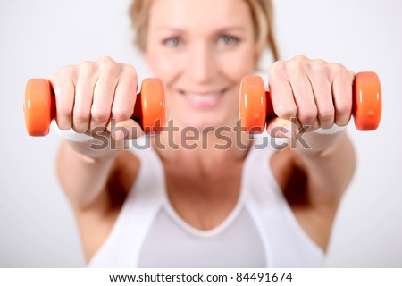 Woman using hand weights during fitness session - stock photo