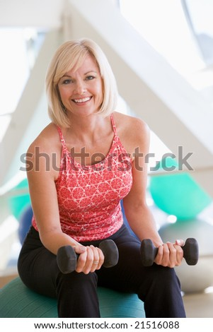 Woman Using Hand Weights On Swiss Ball At Gym - stock photo