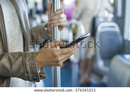 Woman using her cell phone on bus. Sms, message, app - stock photo