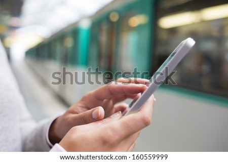Woman using her cell phone on subway platform - stock photo