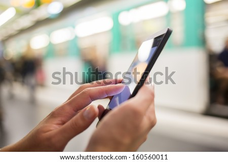 Woman using her cell phone on subway platform, message sms e-mail - stock photo