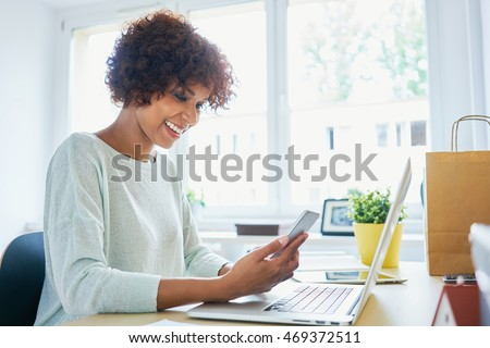 Woman using her cellphone, working from home office