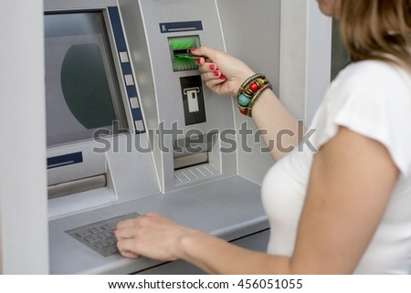 Woman using her credit card on ATM - stock photo