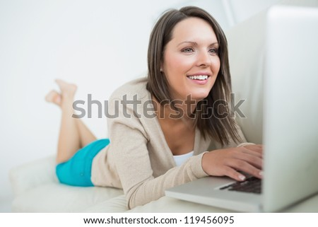 Woman using her laptop and looking happy on sofa in the living room - stock photo