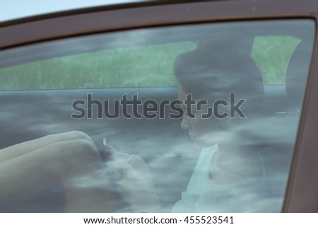 Woman using her phone in car. Evening portrait through autoglass with reflection of the sky and patches of light. - stock photo