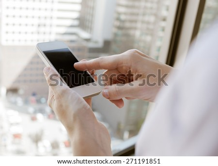 Woman using her phone in the city. - stock photo