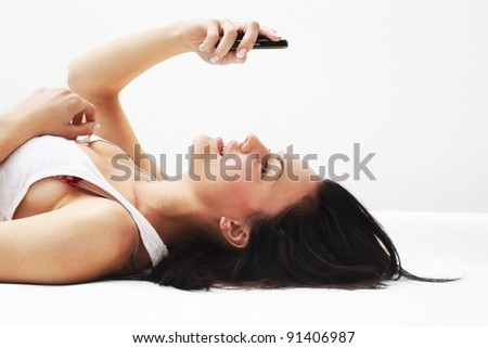 Woman using her phone while lying on her back - stock photo