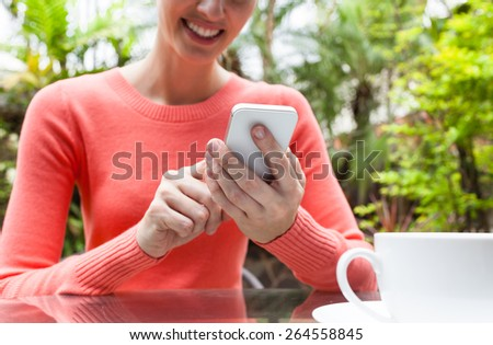Woman using her smartphone and having coffee  - stock photo