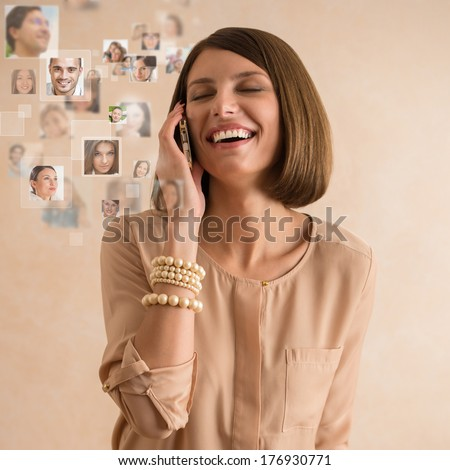 Woman using her smartphone and lots of people portraits around her. Mobile technology concept - stock photo