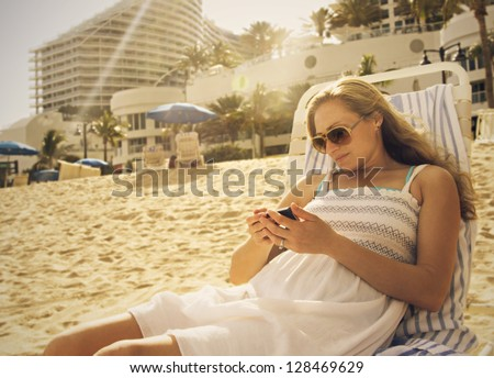 Woman Using her smartphone at the beach - stock photo