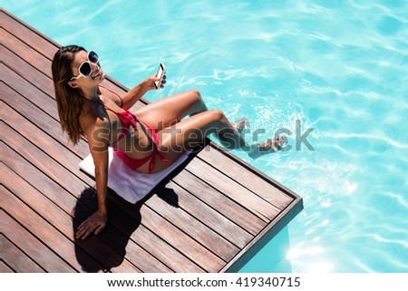 Woman using her smartphone on pool edge on a sunny day - stock photo