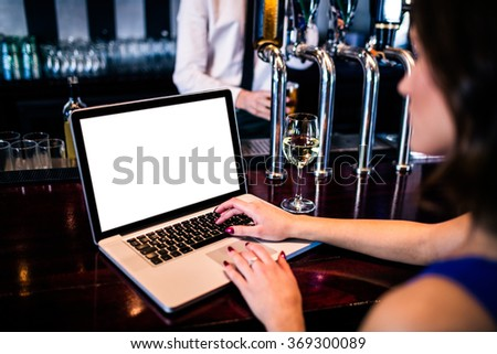 Woman using laptop and having a drink in a bar - stock photo