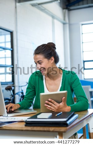 Woman using laptop and holding digital tablet in office
